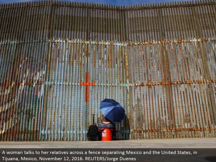 A lady converses with her relatives over a fence isolating Mexico and the United States, in Tijuana,...