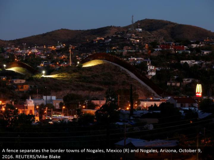 A fence isolates the bordertowns of Nogales, Mexico (R) and Nogales, Arizona, October 9, 2016. REUTERS/Mike Blake
