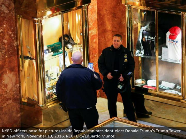 NYPD officers posture for pictures inside Republican president-elect Donald's Trump Tower in New York, November 13, 2016. REUTERS/Eduardo Munoz