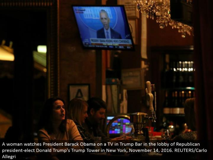 A lady watches President Barack Obama on a TV in Trump Bar in the entryway of Republican president-elect Donald's Trump Tower in New York, November 14, 2016. REUTERS/Carlo Allegri