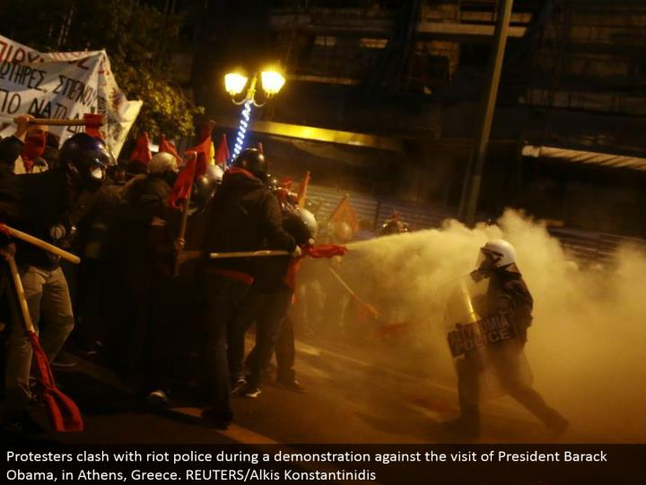 Protesters conflict with mob police amid an exhibit against the visit of President Barack Obama, in ...