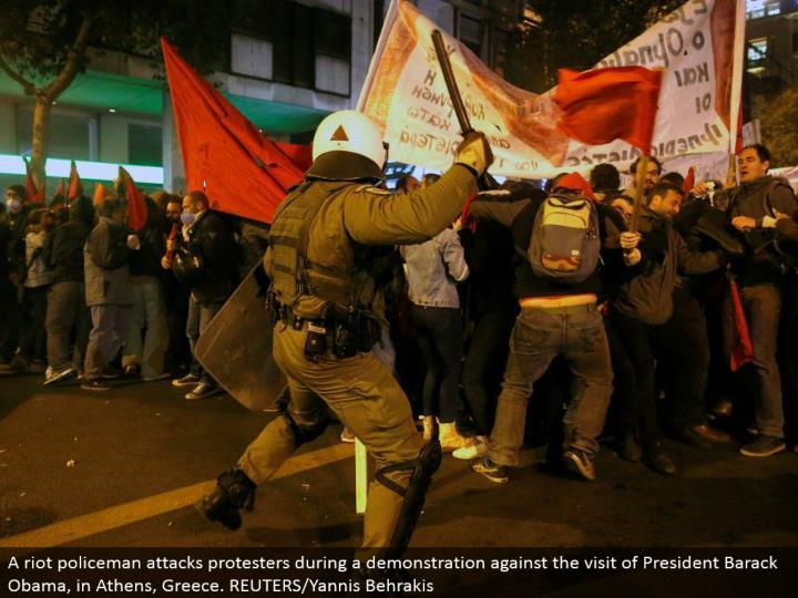 A revolt policeman assaults dissenters amid a show against the visit of President Barack Obama, in A...