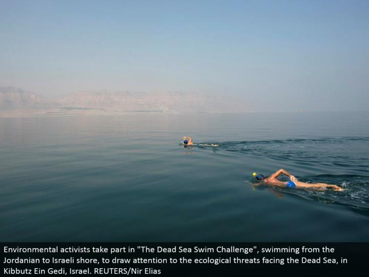 "Environmental activists participate in ""The Dead Sea Swim Challenge"", swimming from the Jordanian to Israeli shore, to attract regard for the natural dangers confronting the Dead Sea, in Kibbutz Ein Gedi, Israel. REUTERS/Nir Elias"