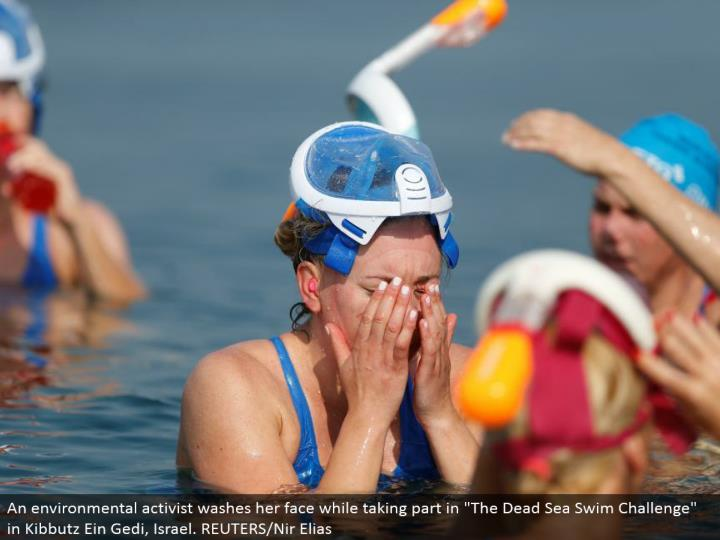 "An ecological dissident washes her face while partaking in ""The Dead Sea Swim Challenge"" in Kibbutz Ein Gedi, Israel. REUTERS/Nir Elias"