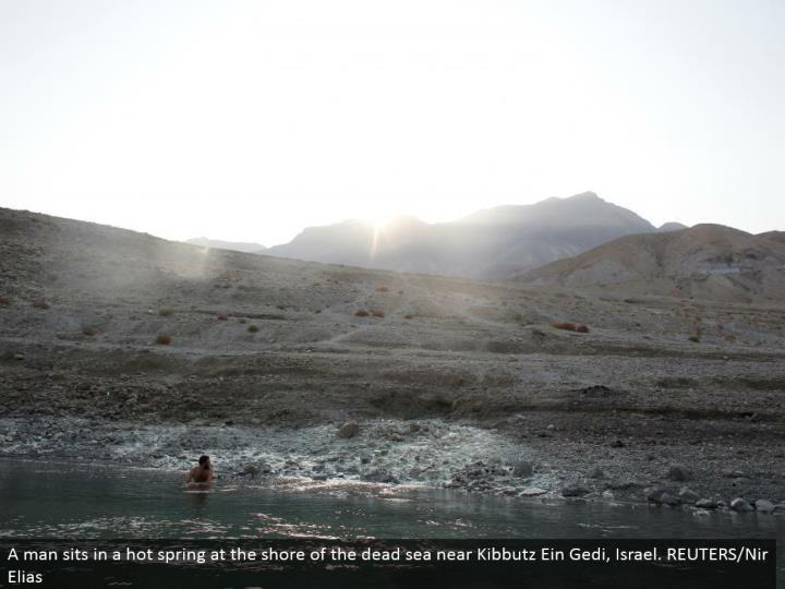 A man sits in a hot spring at the shore of the dead ocean close Kibbutz Ein Gedi, Israel. REUTERS/Nir Elias