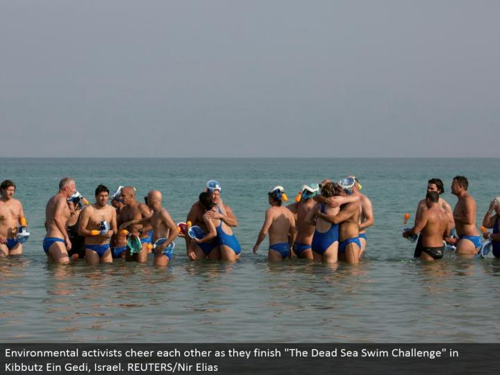 "Environmental activists cheer each different as they complete ""The Dead Sea Swim Challenge"" in Kibbutz Ein Gedi, Israel. REUTERS/Nir Elias"