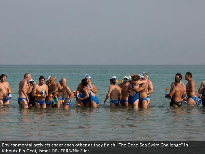 "Environmental activists cheer each different as they complete ""The Dead Sea Swim Challenge"" in Kibbutz Ein Gedi, Israel. REUTERS/Nir Elias"