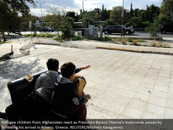 Refugee youngsters from Afghanistan respond as President Barack Obama's motorcade goes by taking after his landing in Athens, Greece. REUTERS/Michalis Karagiannis