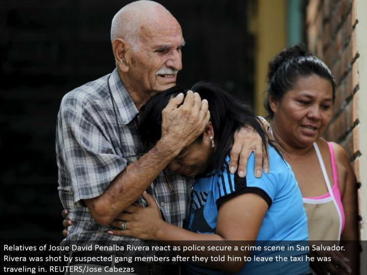 Relatives of Josue David Penalba Rivera respond as police secure a wrongdoing scene in San Salvador. Rivera was shot by speculated group individuals after they instructed him to leave the taxi he was going in. REUTERS/Jose Cabezas