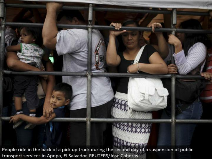 People ride in the back of a get truck amid the second day of a suspension of open transport benefits in Apopa, El Salvador. REUTERS/Jose Cabezas