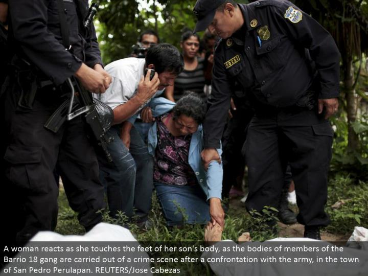 A lady responds as she touches the feet of her child's body, as the collections of individuals from the Barrio 18 posse are completed of a wrongdoing scene after an encounter with the armed force, in the town of San Pedro Perulapan. REUTERS/Jose Cabezas