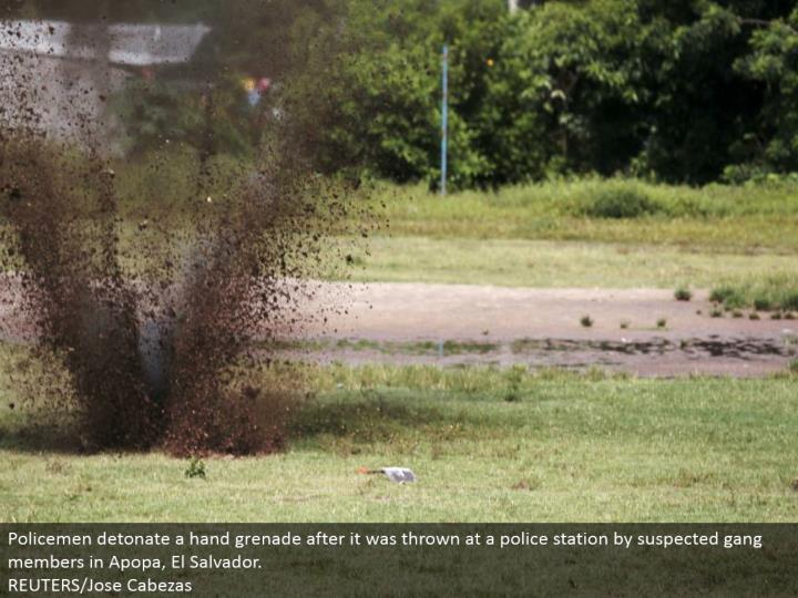 Policemen explode a hand projectile after it was tossed at a police headquarters by presumed pack individuals in Apopa, El Salvador. REUTERS/Jose Cabezas