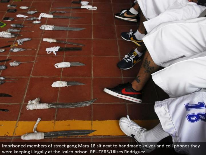 Imprisoned individuals from road posse Mara 18 sit by high quality blades and mobile phones they were keeping unlawfully at the Izalco jail. REUTERS/Ulises Rodriguez