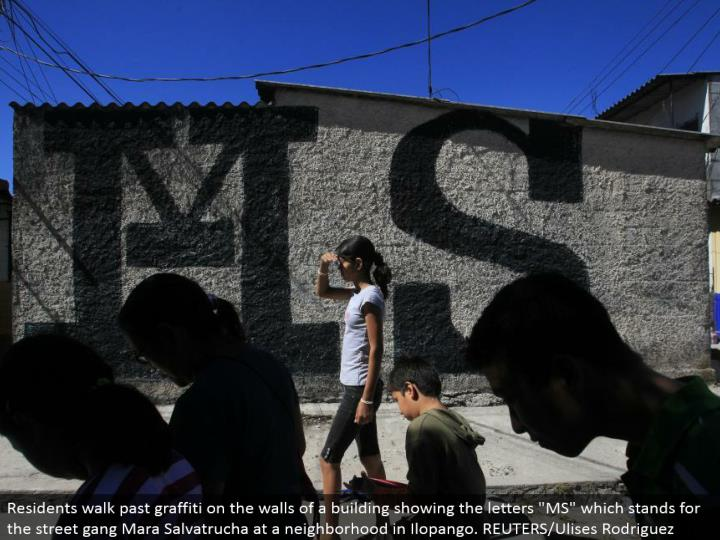 """Residents stroll past spray painting on the dividers of a building demonstrating the letters """"MS"""" which remains for the road group Mara Salvatrucha at an area in Ilopango. REUTERS/Ulises Rodriguez"""