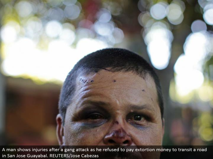 A man demonstrates wounds after a group assault as he declined to pay blackmail cash to travel a street in San Jose Guayabal. REUTERS/Jose Cabezas