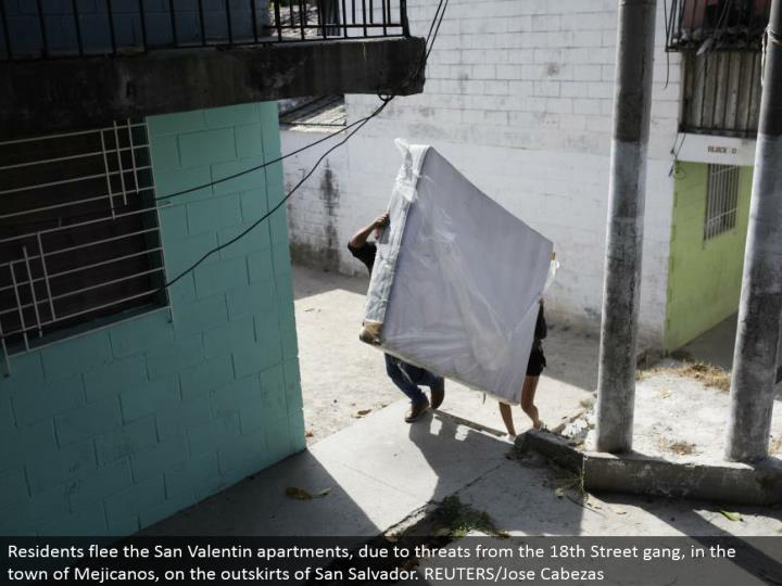 Residents escape the San Valentin flats, because of dangers from the eighteenth Street pack, in the town of Mejicanos, on the edges of San Salvador. REUTERS/Jose Cabezas
