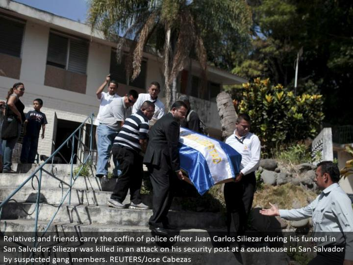 Relatives and companions convey the pine box of cop Juan Carlos Siliezar amid his burial service in San Salvador. Siliezar was murdered in an assault on his security post at a courthouse in San Salvador by speculated pack individuals. REUTERS/Jose Cabezas