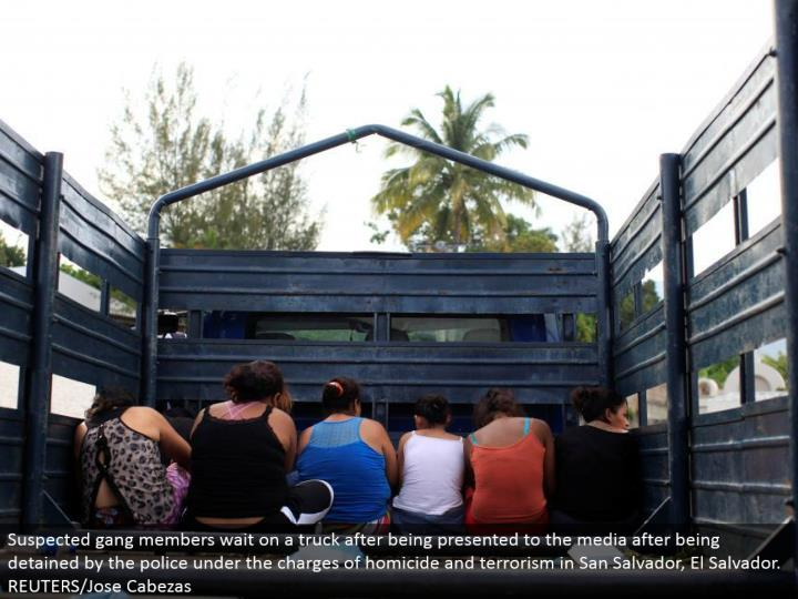 Suspected pack individuals tend to a truck in the wake of being introduced to the media subsequent to being confined by the police under the charges of crime and fear based oppression in San Salvador, El Salvador. REUTERS/Jose Cabezas