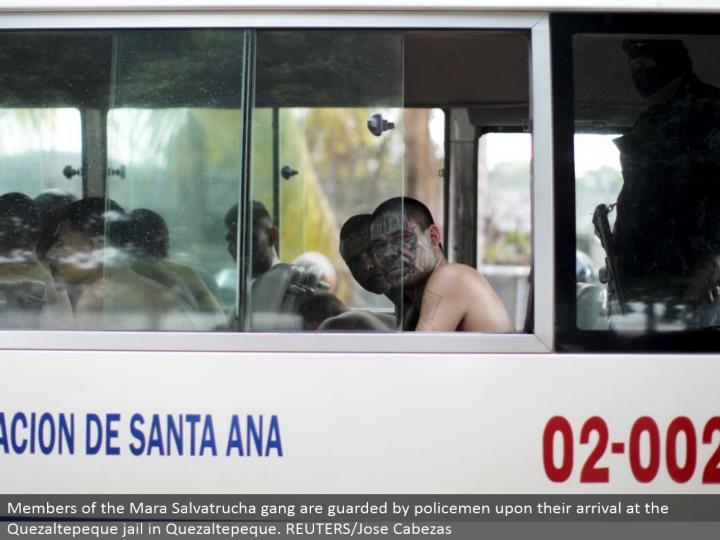 Members of the Mara Salvatrucha posse are monitored by policemen upon their landing in the Quezaltepeque imprison in Quezaltepeque. REUTERS/Jose Cabezas
