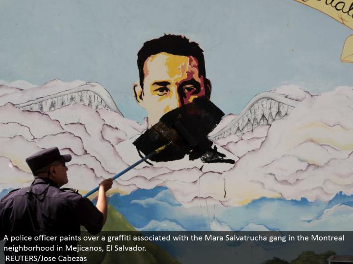 A cop paints over a spray painting connected with the Mara Salvatrucha posse in the Montreal neighborhood in Mejicanos, El Salvador. REUTERS/Jose Cabezas