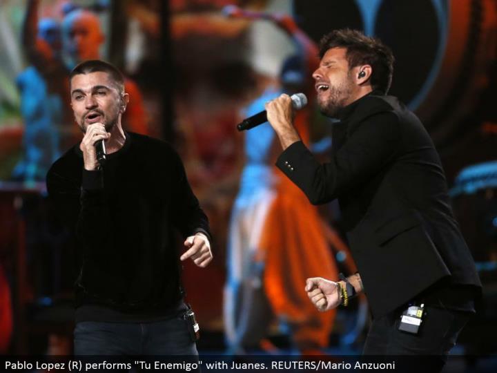 "Pablo Lopez (R) performs ""Tu Enemigo"" with Juanes. REUTERS/Mario Anzuoni"