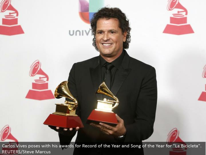 "Carlos Vives postures with his honors for Record of the Year and Song of the Year for ""La Bicicleta"". REUTERS/Steve Marcus"