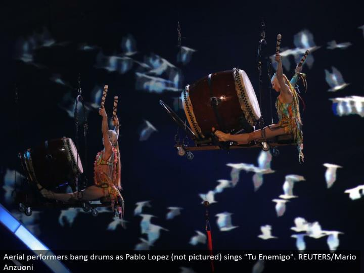 "Aerial entertainers blast drums as Pablo Lopez (not imagined) sings ""Tu Enemigo"". REUTERS/Mario Anzuoni"