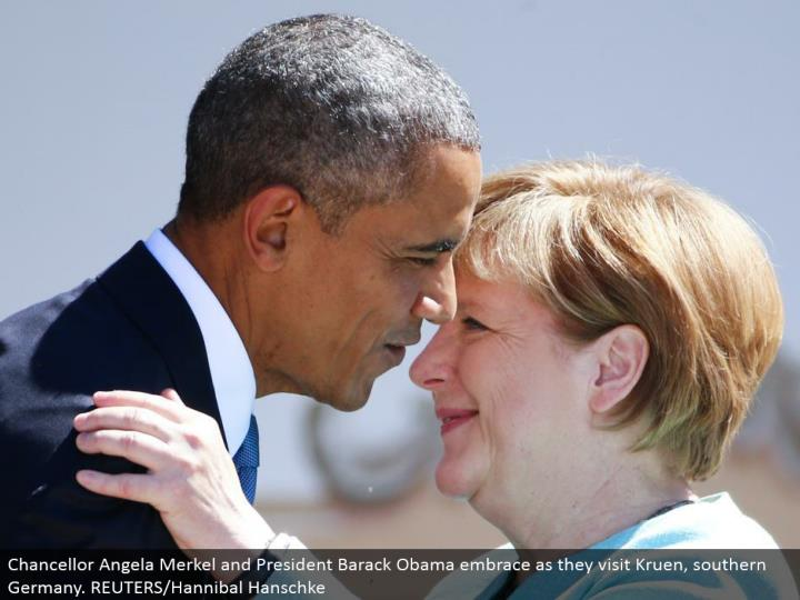 Chancellor Angela Merkel and President Barack Obama hold onto as they visit Kruen, southern Germany. REUTERS/Hannibal Hanschke
