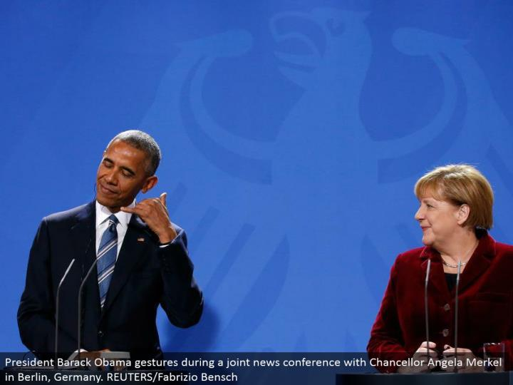 President Barack Obama signals amid a joint news meeting with Chancellor Angela Merkel in Berlin, Germany. REUTERS/Fabrizio Bensch