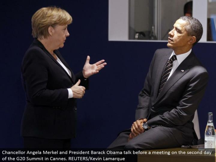 Chancellor Angela Merkel and President Barack Obama talk before a meeting on the second day of the G20 Summit in Cannes. REUTERS/Kevin Lamarque