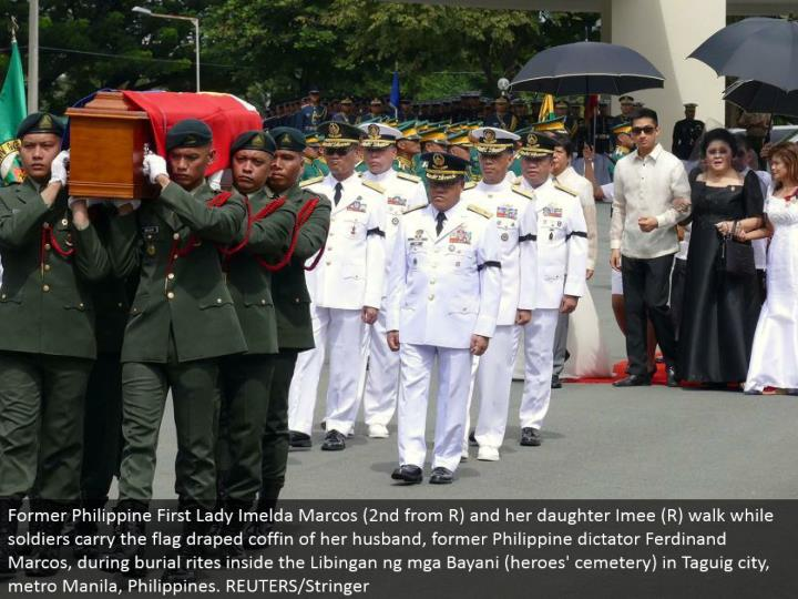 Former Philippine First Lady Imelda Marcos (second from R) and her girl Imee (R) walk while troopers convey the banner hung pine box of her significant other, previous Philippine tyrant Ferdinand Marcos, amid internment customs inside the Libingan ng mga Bayani (legends' burial ground) in Taguig city, metro Manila, Philippines. REUTERS/Stringer