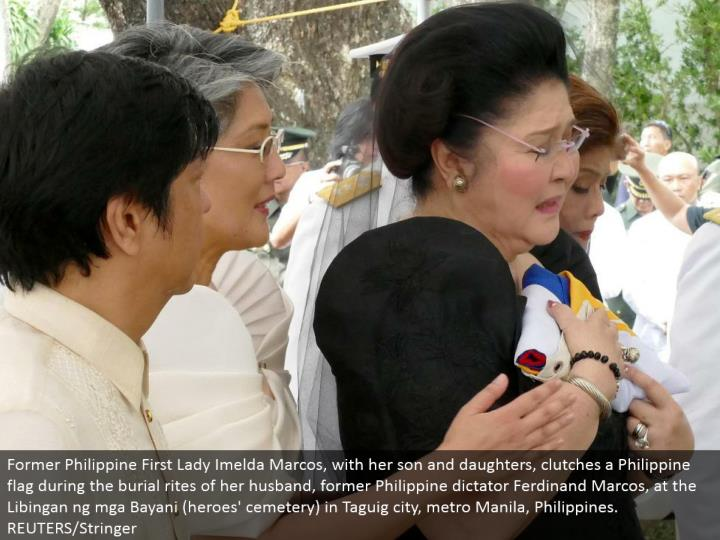 Former Philippine First Lady Imelda Marcos, with her child and little girls, grips a Philippine banner amid the entombment ceremonies of her significant other, previous Philippine tyrant Ferdinand Marcos, at the Libingan ng mga Bayani (legends' graveyard) in Taguig city, metro Manila, Philippines. REUTERS/Stringer