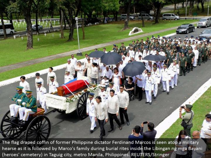 The hail hung pine box of previous Philippine tyrant Ferdinand Marcos is seen on a military funeral ...