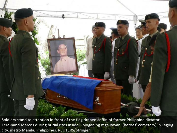 Soldiers remain to consideration before the banner hung pine box of previous Philippine despot Ferdinand Marcos amid entombment customs inside Libingan ng mga Bayani (saints' graveyard) in Taguig city, metro Manila, Philippines. REUTERS/Stringer