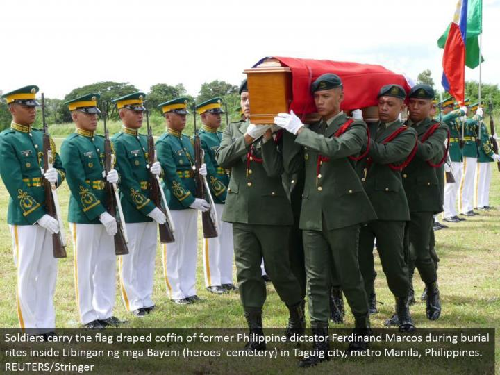 Soldiers convey the banner hung casket of previous Philippine tyrant Ferdinand Marcos amid internment customs inside Libingan ng mga Bayani (saints' graveyard) in Taguig city, metro Manila, Philippines. REUTERS/Stringer