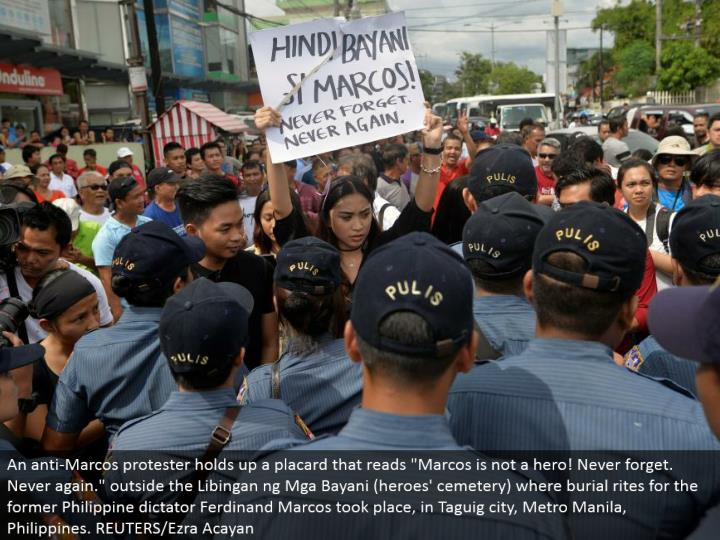 "An hostile to Marcos dissident holds up a notice that peruses ""Marcos is not a legend! Always remember. Never again."" outside the Libingan ng Mga Bayani (legends' graveyard) where internment ceremonies for the previous Philippine tyrant Ferdinand Marcos occurred, in Taguig city, Metro Manila, Philippines. REUTERS/Ezra Acayan"