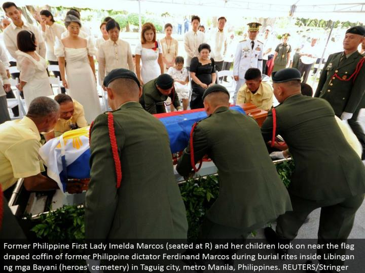 Former Philippine First Lady Imelda Marcos (situated at R) and her kids look on close to the banner hung box of previous Philippine tyrant Ferdinand Marcos amid internment customs inside Libingan ng mga Bayani (legends' burial ground) in Taguig city, metro Manila, Philippines. REUTERS/Stringer