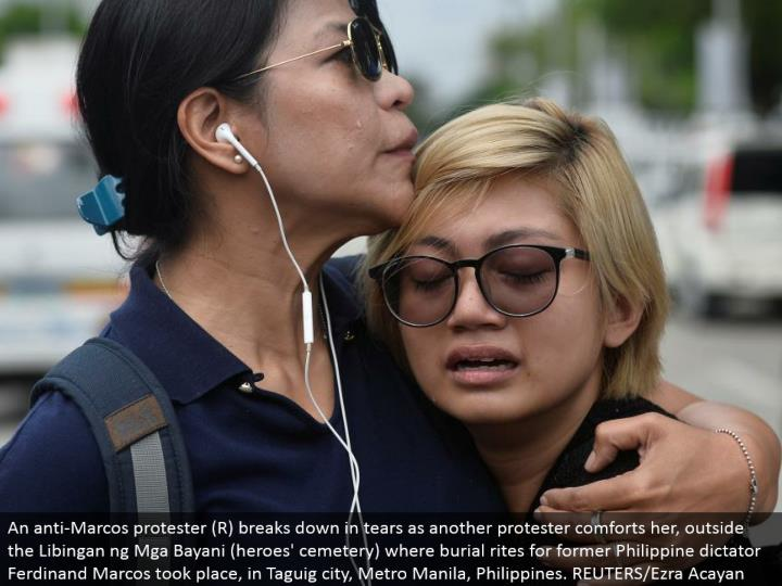 An hostile to Marcos dissenter (R) separates in tears as another nonconformist solaces her, outside the Libingan ng Mga Bayani (legends' graveyard) where internment rituals for previous Philippine despot Ferdinand Marcos occurred, in Taguig city, Metro Manila, Philippines. REUTERS/Ezra Acayan