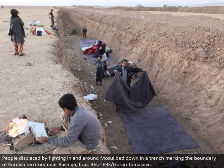 People uprooted by battling in and around Mosul go to sleep in a trench denoting the limit of Kurdish region close Bashiqa, Iraq. REUTERS/Goran Tomasevic