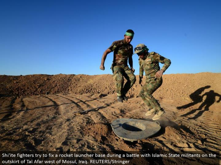 Shi'ite contenders attempt to alter a rocket launcher base amid a fight with Islamic State aggressor...