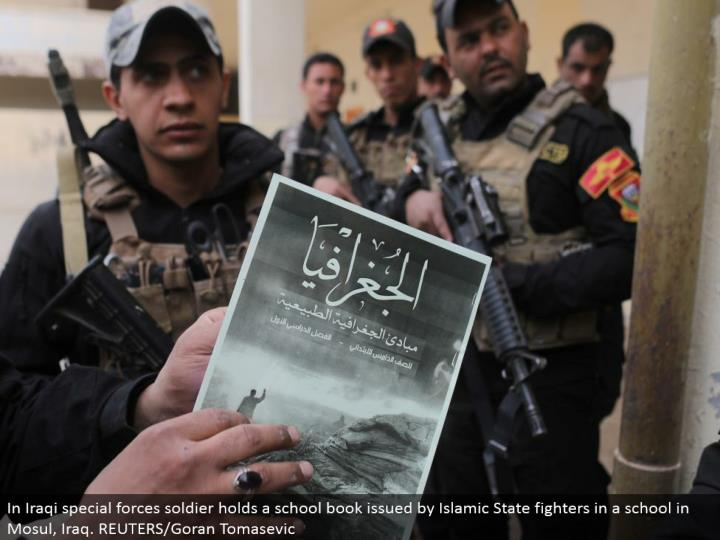 In Iraqi exceptional strengths officer holds a textbook issued by Islamic State contenders in a school in Mosul, Iraq. REUTERS/Goran Tomasevic