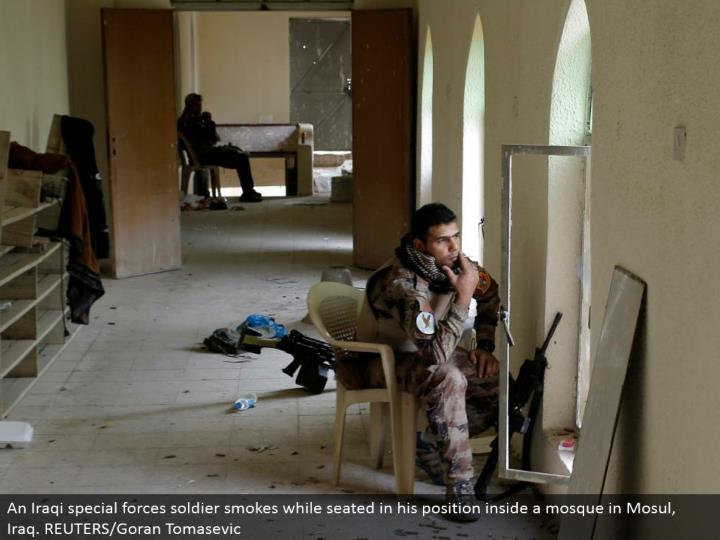 An Iraqi unique powers warrior smokes while situated in his position inside a mosque in Mosul, Iraq. REUTERS/Goran Tomasevic
