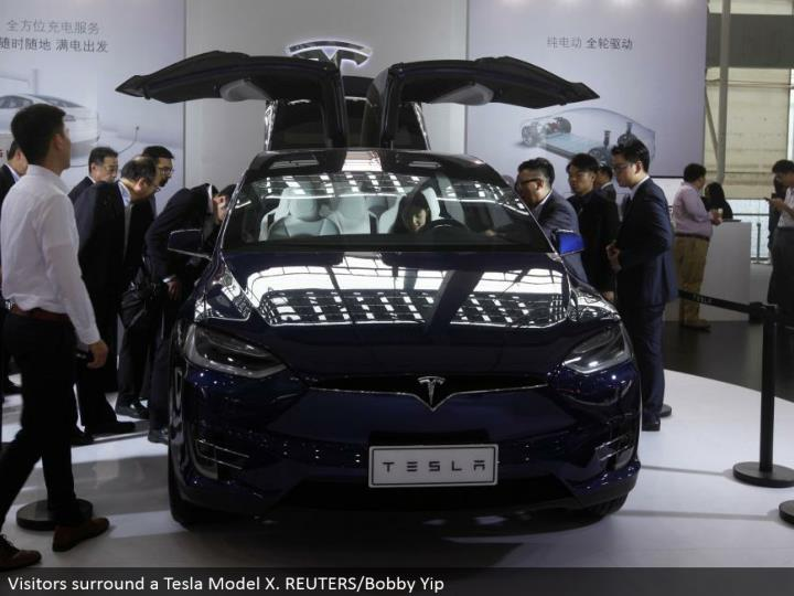 Visitors encompass a Tesla Model X. REUTERS/Bobby Yip