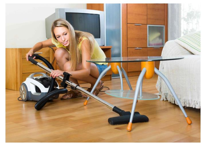 Woman using a canister vacuum to clean hardwood floor