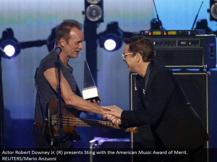 Actor Robert Downey Jr. (R) presents Sting with the American Music Award of Merit. REUTERS/Mario Anzuoni