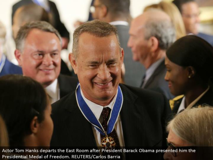 Actor Tom Hanks leaves the East Room after President Barack Obama displayed him the Presidential Medal of Freedom. REUTERS/Carlos Barria