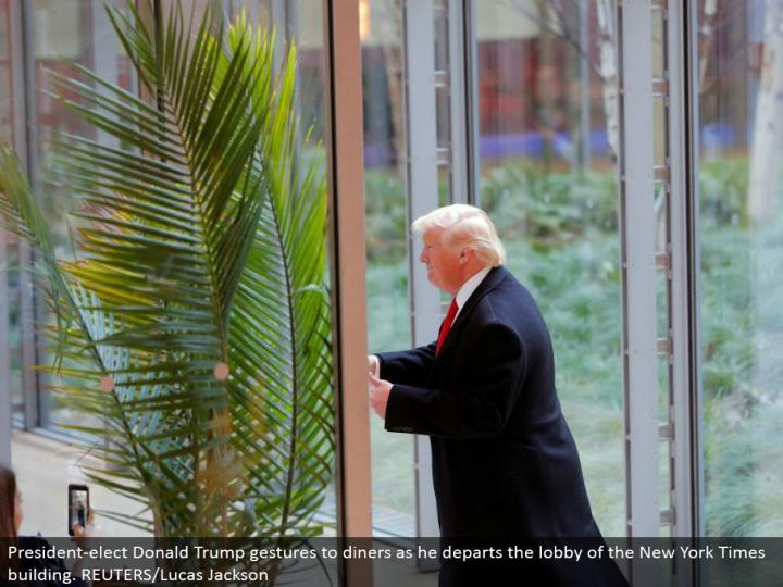 President-choose Donald Trump signals to cafes as he leaves the entryway of the New York Times building. REUTERS/Lucas Jackson