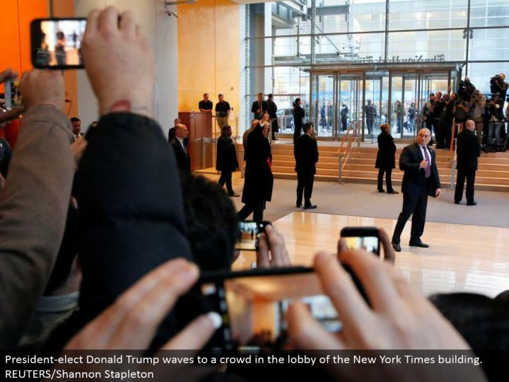 President-choose Donald Trump waves to a swarm in the entryway of the New York Times building. REUTERS/Shannon Stapleton