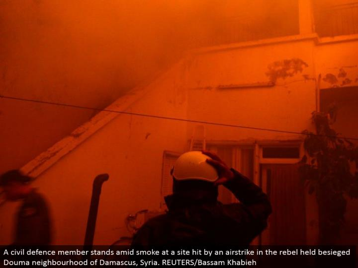 A common resistance part remains in the midst of smoke at a site hit by an airstrike in the revolt h...