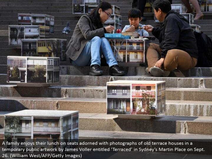 "A family makes the most of their lunch on seats decorated with photos of old porch houses in a transitory open work of art by James Voller entitled ""Terraced"" in Sydney's Martin Place on Sept. 26. (William West/AFP/Getty Images)"